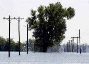 Floodwater covers state highway HH lined by utility poles following the Army Corps of Engineers intentional breach of the Birds Point levee Wednesday, May 4, 2011, in Wyatt, Mo.  The breach by the Corps on Monday flooded 130,000 acres of mostly farmland in southeastern Missouri. (AP Photo/Jeff Roberson)