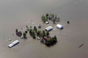 A farm is seen surrounded by floodwater Tuesday, May 3, 2011, in Mississippi County, Mo. The Army Corps of Engineers' blew a two-mile hole into the Birds Point levee in southeast Missouri, after nightfall Monday, flooding 130,000 acres of farmland in Missouri's Mississippi County in an effort to protect nearby Cairo, Ill.« Read less (AP Photo/Jeff Roberson)