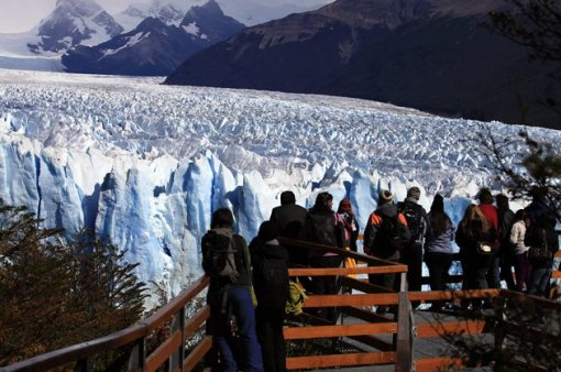 Tourists look at the Perito Moreno glacier after the rupture of a massive ice wall near the city of El Calafate in the Patagonian province of Santa Cruz, southern Argentina, March 4, 2012. The glacier, a massive tongue of ice in the Santa Cruz province that covers 250 square kilometres (97 square miles), advances yearly into a lake, known as Lago Argentino. As Perito Moreno moves forward, it cuts off a river feeding the lake. Water builds up pressure and slowly undermines the ice, forming a tunnel until ice comes tumbling down. The phenomenon repeats itself at irregular intervals, with the last major ice falls occurring in 2008. REUTERS/Andres Arce (ARGENTINA - Tags: ENVIRONMENT TRAVEL)