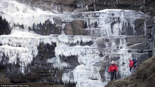 Water not-quite-fall: Climbers Simon Stokes and Mark Davies admire giant icicles along the frozen Kinder Downfall waterfall high in the Derbyshire Peak District