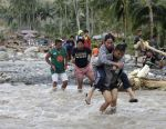 Residents cross a river in the flash flood-hit village of Andap, New Bataan township, Compostela Valley in southern Philippines Wednesday, Dec. 5, 2012. (AP Photo/Bullit Marquez)