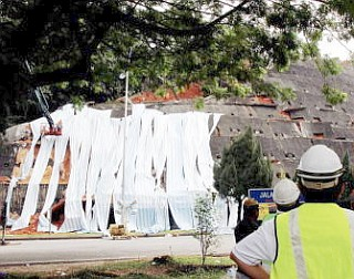 Hard at work: Workers covering the partially collapsed wall in Bukit Setiawangsa with a canvas.