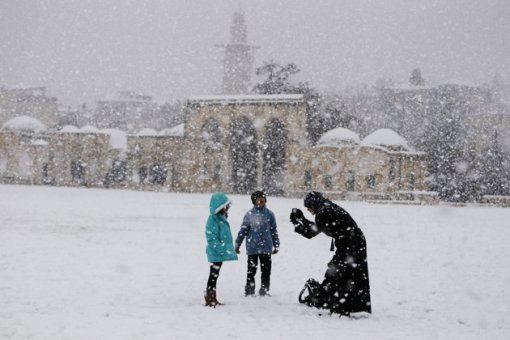 Palestinians stand on the compound known to Muslims as al-Haram al-Sharif in Jerusalem's Old City during a snowstorm January 10, 2013. The worst snowstorm in 20 years shut government offices, public transport and schools in Jerusalem and along the northern Israeli region bordering on Lebanon on Thursday. REUTERS/Ammar Awad