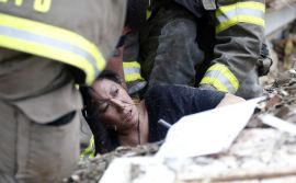 A woman is pulled out from under tornado debris at the Plaza Towers School in Moore, Okla., Monday, May 20, 2013. A tornado as much as a mile (1.6 kilometers) wide with winds up to 200 mph (320 kph) roared through the Oklahoma City suburbs Monday, flattening entire neighborhoods, setting buildings on fire and landing a direct blow on an elementary school. (AP Photo Sue Ogrocki)