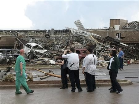 People look at the destruction after a huge tornado struck Moore, Oklahoma May 20, 2013. A huge tornado with winds of up to 200 miles per hour devastated the Oklahoma City suburb of Moore on Monday, ripping up at least two elementary schools and a hospital and leaving a wake of tangled wreckage. At least four people were killed, KFOR television said, citing a reporter's eyewitness account, and hospitals said dozens of people were injured as the dangerous storm system threatened as many as 10 U.S. states with more twisters. REUTERS/Gene Blevins (UNITED STATES – Tags: ENVIRONMENT DISASTER)