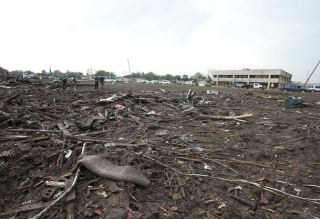 Parts of trees and household debris cover the ground after a huge tornado struck Moore, Oklahoma, near Oklahoma City, May 20, 2013. A massive tornado tore through the Oklahoma City suburb of Moore on Monday, killing at least 51 people as winds of up to 200 miles per hour (320 kph) flattened entire tracts of homes, two schools and a hospital, leaving a wake of tangled wreckage. REUTERS/Richard Rowe (UNITED STATES – Tags: DISASTER ENVIRONMENT