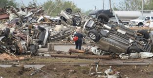A rescue worker looks for victims in the Moore Hospital parking lot after being hit by a tornado that destroyed buildings and overturned cars in Moore, Oklahoma, near Oklahoma City, May 20, 2013. A huge tornado with winds of up to 200 miles per hour (320 kph) devastated the Oklahoma City suburb of Moore on Monday, ripping up at least two elementary schools and a hospital and leaving a wake of tangled wreckage. At least four people were killed, KFOR television said, citing a reporter's eyewitness account, and hospitals said dozens of people were injured. REUTERS/Gene Blevins (UNITED STATES – Tags: DISASTER ENVIRONMENT)