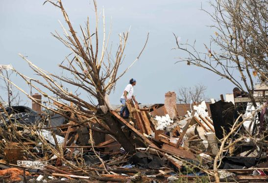 A man looks through the remains of a home after a huge tornado struck Moore, Oklahoma, near Oklahoma City, May 20, 2013. A massive tornado tore through the Oklahoma City suburb of Moore on Monday, killing at least 51 people as winds of up to 200 miles per hour (320 kph) flattened entire tracts of homes, two schools and a hospital, leaving a wake of tangled wreckage. REUTERS/Richard Rowe (UNITED STATES – Tags: DISASTER ENVIRONMENT