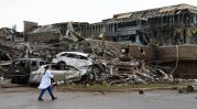A nurse walks past the destruction at Moore hospital after a huge tornado struck Moore, Oklahoma, near Oklahoma City, May 20, 2013. A huge tornado with winds of up to 200 miles per hour (320 kph) devastated the Oklahoma City suburb of Moore on Monday, ripping up at least two elementary schools and a hospital and leaving a wake of tangled wreckage. REUTERS/Gene Blevins (UNITED STATES – Tags: DISASTER ENVIRONMENT TPX IMAGES OF THE DAY)