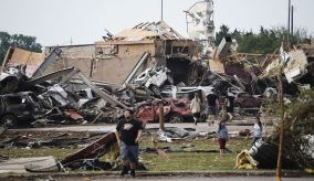 People walk near destroyed buildings and vehicles after a tornado struck Moore, Oklahoma, near Oklahoma City, May 20, 2013. At least 91 people, including 20 children, were feared killed when a 2 mile wide tornado tore through the Oklahoma City suburb of Moore, trapping victims beneath the rubble as one elementary school took a direct hit and another was destroyed. REUTERS/Gene Blevins (UNITED STATES – Tags: ENVIRONMENT DISASTER)