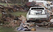 Kay James holds her cat as she sits in her driveway after her home was destroyed by the tornado that hit the area on Monday, May 20, 2013 in Oklahoma City, Okla. (AP Photo/The Oklahoman, Chris Landsberger)