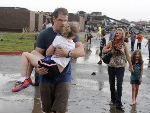 Teachers carry children away from Briarwood Elementary school after a tornado destroyed the school in south Oklahoma City, Monday, May 20, 2013. A monstrous tornado roared through the Oklahoma City suburbs, flattening entire neighborhoods with winds up to 200 mph, setting buildings on fire and landing a direct blow on an elementary school. (AP Photo/The Oklahoman, Paul Hellstern)