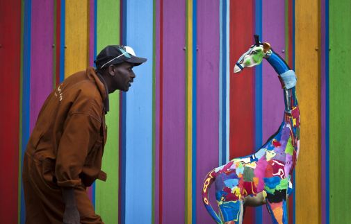 In this photo taken Monday, April 29, 2013, carver Jackson Mbatha, 40, poses next to an unfinished large toy giraffe he is making from pieces of discarded flip-flops, in front of a painted workshop wall at the Ocean Sole flip-flop recycling company in Nairobi, Kenya. The company is cleaning the East African country's beaches of used, washed-up flip-flops and the dirty pieces of rubber that were once cruising the Indian Ocean's currents are now being turned into colorful handmade giraffes, elephants and other toy animals. (AP Photo/Ben Curtis)
