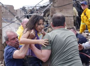 A child is pulled from the rubble of the Plaza Towers Elementary School in Moore, Okla., and passed along to rescuers Monday, May 20, 2013. A tornado as much as a mile (1.6 kilometers) wide with winds up to 200 mph (320 kph) roared through the Oklahoma City suburbs Monday, flattening entire neighborhoods, setting buildings on fire and landing a direct blow on an elementary school.(AP Photo Sue Ogrocki)