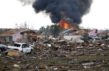 A fire burns in the Tower Plaza Addition in Moore, Okla., following a tornado Monday, May 20, 2013. A tornado as much as a mile wide with winds up to 200 mph roared through the Oklahoma City suburbs Monday, flattening entire neighborhoods, setting buildings on fire and landing a direct blow on an elementary school. (AP Photo Sue Ogrocki