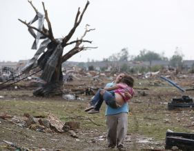 A woman carries her child through a field near the collapsed Plaza Towers Elementary School in Moore, Okla., Monday, May 20, 2013. A tornado as much as a mile (1.6 kilometers) wide with winds up to 200 mph (320 kph) roared through the Oklahoma City suburbs Monday, flattening entire neighborhoods, setting buildings on fire and landing a direct blow on an elementary school. (AP Photo Sue Ogrocki)
