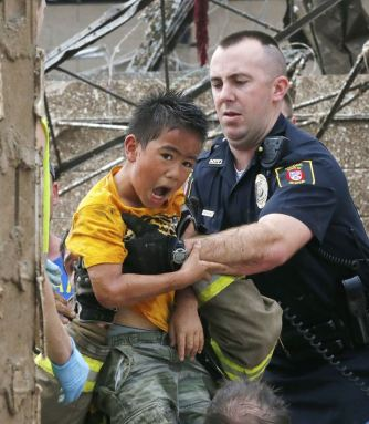 A boy is pulled from beneath a collapsed wall at the Plaza Towers Elementary School following a tornado in Moore, Okla., Monday, May 20, 2013. A tornado as much as a mile (1.6 kilometer) wide with winds up to 200 mph (320 kph) roared through the Oklahoma City suburbs Monday, flattening entire neighborhoods, setting buildings on fire and landing a direct blow on the elementary school. (AP Photo Sue Ogrocki)
