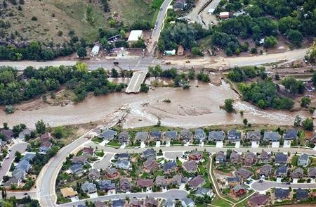 An aerial view shows flood waters and a washed-out road adjacent a suburban neighborhood in Lyons, Colorado September 13, 2013. REUTERS/John Wark