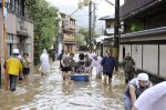 "Guests at a Japanese inn are rescued by boat along a flooded road after tropical storm Man-yi, locally named Typhoon No.18, made landfall in Kyoto, western Japan, in this photo taken by Kyodo September 16, 2013. Torrential rain hit western Japan on Monday morning as Man-yi made landfall in the country's central region, prompting the weather agency to warn of ""unprecedented heavy rain"" and urge people to take safety precautions. In Kyoto Prefecture, some 260,000 residents were ordered to evacuate, including about 81,000 in Fukuchiyama, Kyodo news reported. Mandatory Credit. REUTERS/Kyodo"