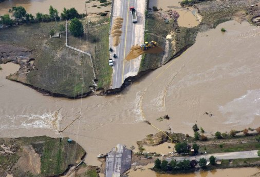 A road crew works on a stretch of highway washed out by flooding along the South Platte River in Weld County, Colorado near Greeley, Saturday, Sept. 14, 2013. Hundreds of roads in the area have been damaged or destroyed by the floodwaters that have affected parts of a 4,500-square-mile (11,655-square-kilometer) area — an area the size of the U.S. state of Connecticut. (AP Photo/John Wark