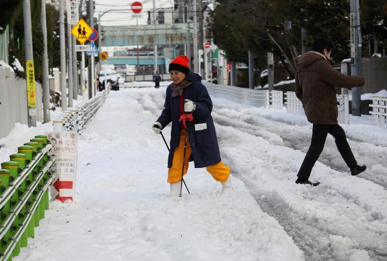 A woman crosses a snow-covered road assisted with walking sticks in Tokyo on February 9, 2014 (AFP Photo/Yoshikazu Tsuno)