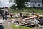 Debris from Tuesday's storm sits along a road on Wednesday, July 9, 2014, in Smithfield, N.Y. (AP Photo/Mike Groll)
