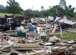 People sort through debris of a destroyed house after Tuesday night's storm, on Wednesday, July 9, 2014, in Smithfield, N.Y. The National Weather Service has confirmed that a tornado destroyed the homes in upstate New York where four people were killed. (AP Photo/Mike Groll)