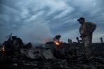 People walk amongst the debris, at the crash site of a passenger plane near the village of Grabovo, Ukraine. Photo / AP