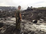 An armed pro-Russian separatist stands at a site of a Malaysia Airlines Boeing 777 plane crash in the settlement of Grabovo in the Donetsk region, July 17, 2014. (Photo REUTERS/Maxim Zmeyev).