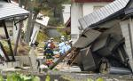 Firefighters and rescuers examine buildings collapsed after a strong earthquake hit Hakuba, Nagano prefecture, central Japan, Sunday, Nov. 23, 2014. (AP Photo/Kyodo News)