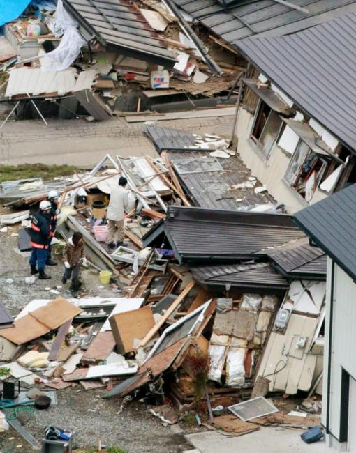 This aerial photo shows collapsed houses after a strong earthquake hit Hakuba, Nagano prefecture, central Japan, Sunday, Nov. 23, 2014. (AP Photo/Kyodo News)
