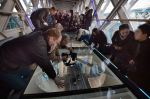 Members of the media capture the view from the newly installed glass floor. (PA)