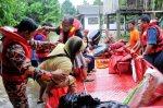 PENGARAH Jabatan Pegawai Bomba dan Penyelamat Kelantan, Azmi Osman (kanan) membantu penduduk kawasan Kampung Tiong mengangkat barang ke dalam bot penyelamat bomba untuk dipindahkan ke pusat pemindahan sementara SK Tiong, Kota Bharu. - Foto Nik Abdullah Nik Omar/Berita Harian.