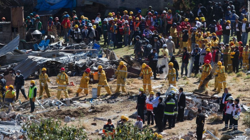 Rescue workers form a human chain, passing buckets of rubble, as they clear the wreckage of a children's hospital, caused by a gas tank truck explosion in Cuajimalpa on the outskirts of Mexico City, Thursday, Jan. 29, 2015.The powerful explosion shattered the hospital on the western edge of Mexico's capital, killing at least two and injuring dozens. (AP Photo)