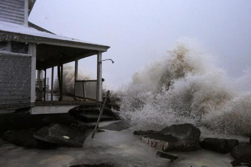 Waves crash against an ocean front house after causing a break in the sea wall during a winter blizzard in Marshfield, Massachusetts January 27, 2015. REUTERS/Brian Snyder
