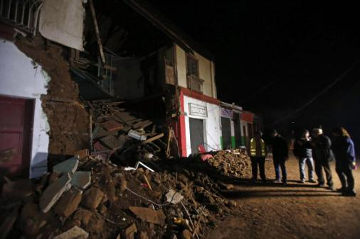 People stand outside a destroyed house in Illapel, Chile, Thursday, Sept. 17, 2015. A magnitude 8.3 earthquake hit off northern Chile on Wednesday night, causing buildings to sway in the capital of Santiago and prompting authorities to issue a tsunami warning for the Andean nation's entire Pacific coast. People sought safety in the streets of inland cities, while others along the shore took to their cars to get to higher ground. (AP Photo/Luis Hidalgo)