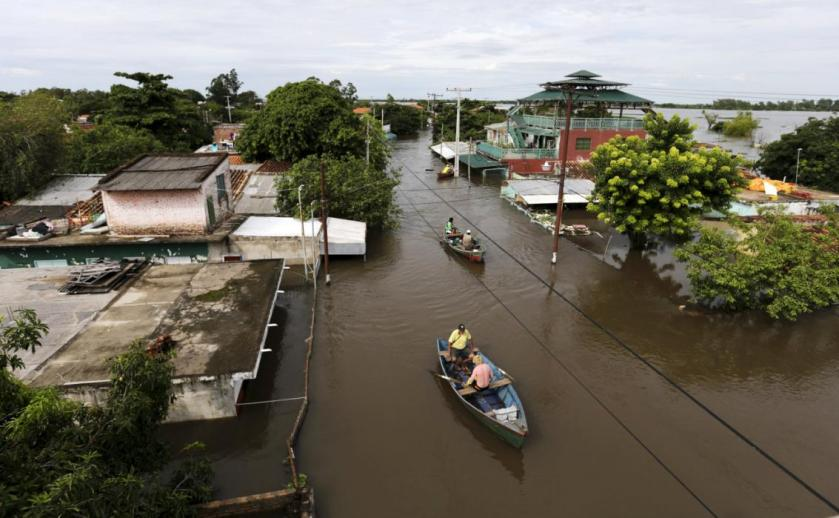 Men travel on a boat near flood-affected houses in Asuncion, December 27, 2015. More than 100,000 people have had to evacuate from their homes in the bordering areas of Paraguay, Uruguay, Brazil and Argentina due to severe flooding in the wake of heavy summer rains brought on by El Niño, authorities said on Saturday. REUTERS/Jorge Adorno