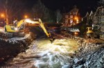 Early this morning diggers were seen desperately trying to stem the flow of raging flood waters after a nearby river burst its banks again. (Photo by DailyMail)