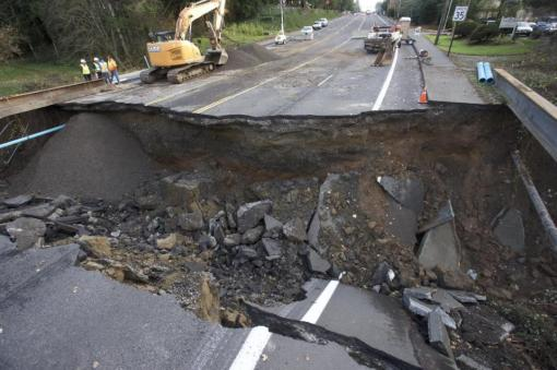 Maintenance personnel look at a large sinkhole on Kane Drive in Gresham, Ore., Wednesday, Dec. 9, 2015. Torrential rains pummeled parts of the Pacific Northwest early Wednesday, causing mudslides and flooding roads. (AP Photo/Steve Dipaola)