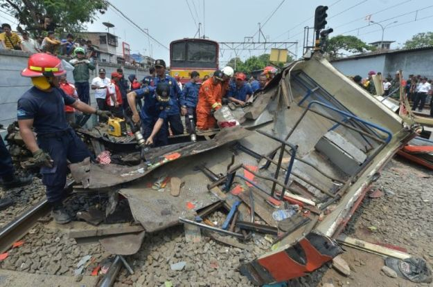 Indonesian firefighters cut into the wreckage of a minibus after it collided with a train in Jakarta on December 6, 2015 1 / 1AFP   Photo by Adek Berry / AFP