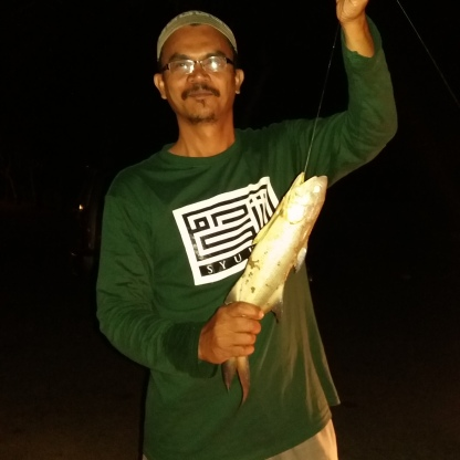 An angler proudly showed the fish that he caught at river side by the Masjid Sultan Ibrahim.