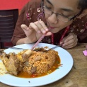 Using a straw to sip in the bone marrow server with the 'Nasi Goreng Racun'