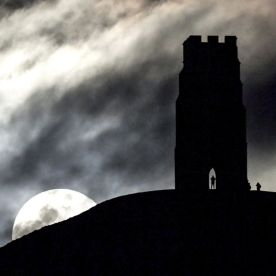 The moon rises behind Glastonbury Tor, southwestern England. This is the second full moon of the month, commonly known as a 'blue moon', and won't happen again for another two years and eight months. (Ben Birchall/PA via AP)
