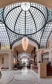 """Guests of this Art Nouveau treasure, located on the banks of the Danube River, are greeted by a sprawling white-and-aqua-blue glass atrium in the hotel's lobby. The glass ceiling, described by the hotel as """"a true labor of love,"""" was designed to enclose what was originally a horse-and-carriage drop-off for the palace."""