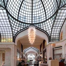 "Guests of this Art Nouveau treasure, located on the banks of the Danube River, are greeted by a sprawling white-and-aqua-blue glass atrium in the hotel's lobby. The glass ceiling, described by the hotel as ""a true labor of love,"" was designed to enclose what was originally a horse-and-carriage drop-off for the palace."