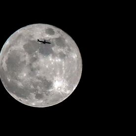 A plane is silhouetted by the Blue Moon as it passes over Liverpool, Merseyside. (PA)
