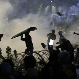 Protesters throw rocks and other objects towards police [Achmad Ibrahim/AP Photo]