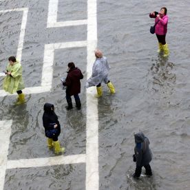 People walk through flood waters in St. Mark's Square on Tuesday.Luca Bruno/AP